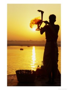 bn19268_11priest-moves-lantern-in-front-of-sun-during-morning-puja-on-ganga-ma-varanasi-india-posters